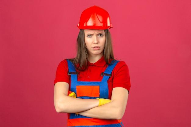 Jonge vrouw in bouw eenvormige en rode veiligheidshelm die zich met gekruiste wapens bevinden die uitdrukking op gezicht op donkere roze achtergrond afkeuren