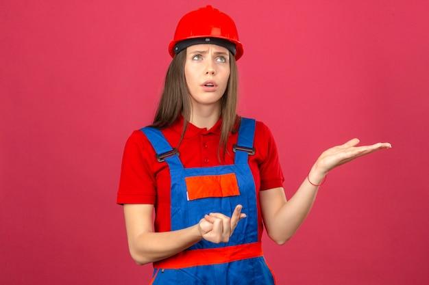 Jonge vrouw in bouw eenvormige en rode veiligheidshelm die zijweg tellen en denken die zich op donkere roze achtergrond denken denken