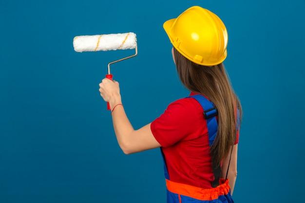 Jonge vrouw in bouw uniforme en gele veiligheidshelm houden verfrol staande op blauwe achtergrond