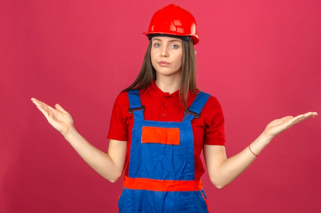 Jonge vrouw in bouw uniforme en rode veiligheidshelm clueless en verwarde uitdrukking met opgeheven armen en handen zonder idee expressie staande op donkerroze achtergrond
