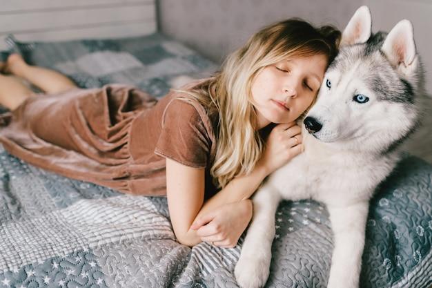 Jonge vrouw in bruine kleding die op schor puppy op bed ligt.