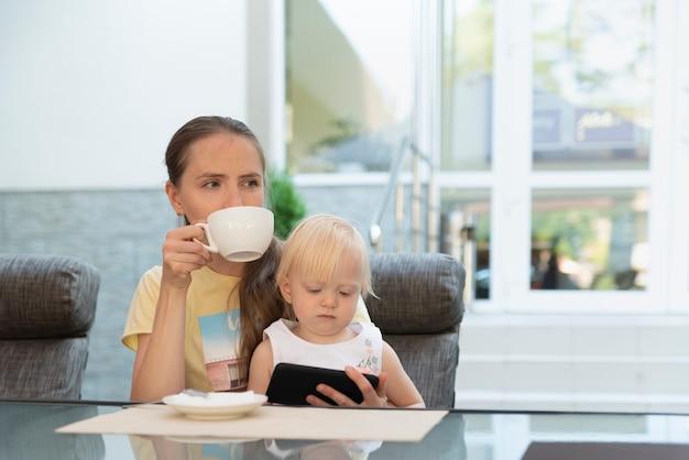 Jonge vrouw in café drinkt een kopje koffie terwijl het kind in haar armen naar de telefoon kijkt