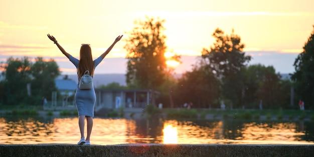 Jonge vrouw in casual outfit ontspannen aan de kant van het meer met opgeheven handen op warme avond. succes en wellness-concept.