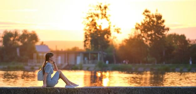 Jonge vrouw in casual outfit ontspannen aan de kant van het meer op warme avond. zomervakanties en reizen concept.