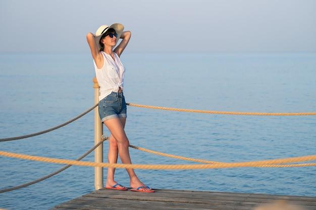 Jonge vrouw in casual outfit ontspannen aan zee op warme zomerdag.