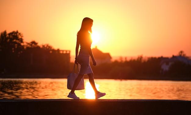 Jonge vrouw in casual outfit wandelen aan de kant van het meer op warme avond. zomervakanties en reizen concept.