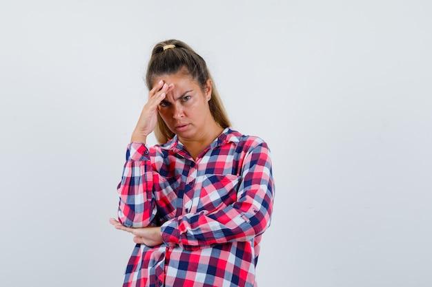 Jonge vrouw in casual overhemd hand boven het hoofd houden en op zoek verontrust, vooraanzicht.