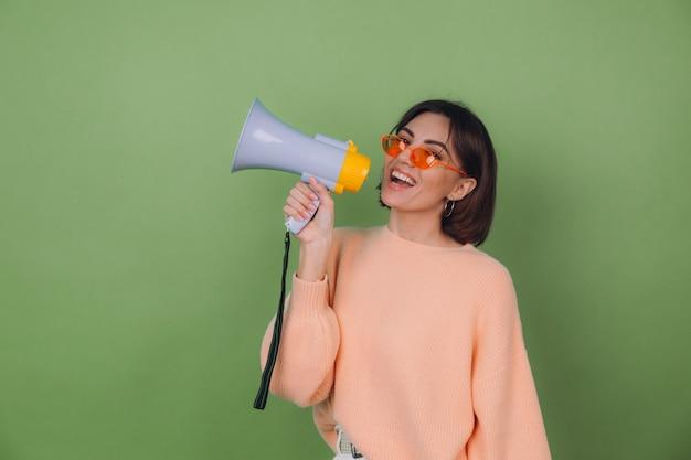Jonge vrouw in casual perzik en oranje bril trui geïsoleerd op groene olijf muur gelukkig schreeuwen in megafoon kopie ruimte