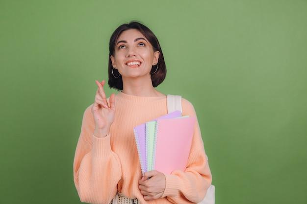 Jonge vrouw in casual perzik trui en rugzak geïsoleerd op groene olijf kleur muur