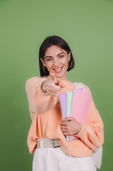 Jonge vrouw in casual perzik trui en rugzak geïsoleerd op groene olijf kleur muur Gratis Foto