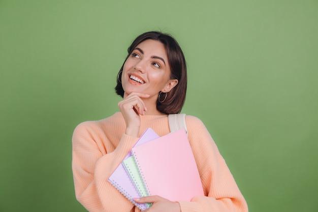 Jonge vrouw in casual perzik trui geïsoleerd op groene olijf kleur muur