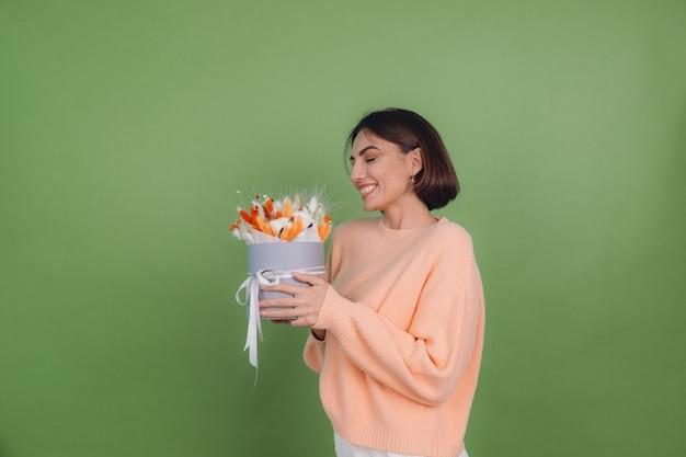 Jonge vrouw in casual perzik trui geïsoleerd op groene olijf muur houden oranje witte bloembak samenstelling van katoen bloemen gypsophila tarwe en lagurus voor een geschenk blij verbaasd verrast