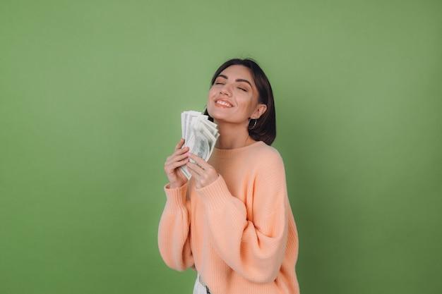 Jonge vrouw in casual perziksweater die op groene olijfmuur wordt geïsoleerd Premium Foto