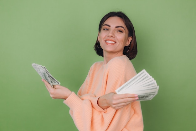 Jonge vrouw in casual perziksweater die op groene olijfmuur wordt geïsoleerd