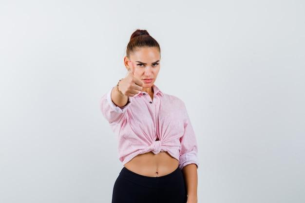 Jonge vrouw in casual shirt, broek duim opdagen en op zoek trots, vooraanzicht.