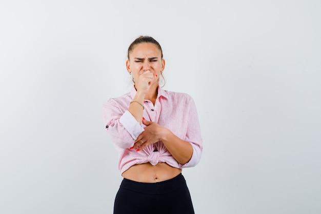 Jonge vrouw in casual shirt, broek hoest lijden en ziek kijken