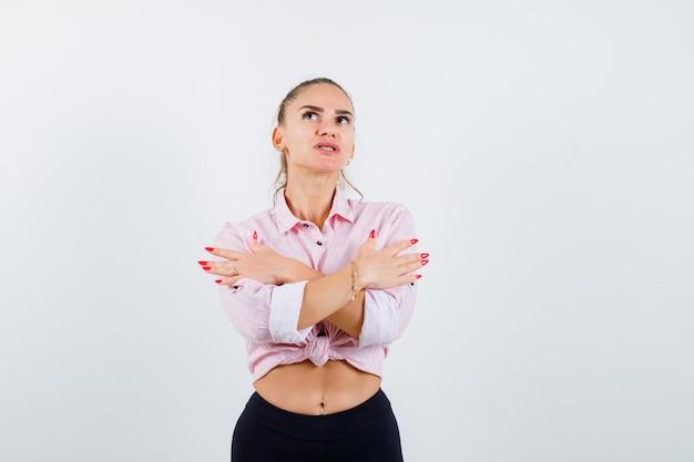Jonge vrouw in casual shirt knuffelen zichzelf en op zoek doordachte, vooraanzicht.