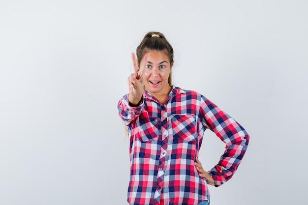 Jonge vrouw in casual shirt met overwinning gebaar en op zoek gelukkig, vooraanzicht.