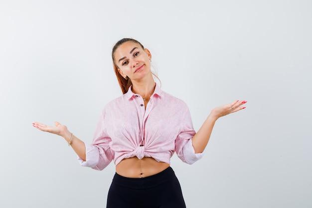 Jonge vrouw in casual shirt schalen gebaar maken en aarzelend op zoek