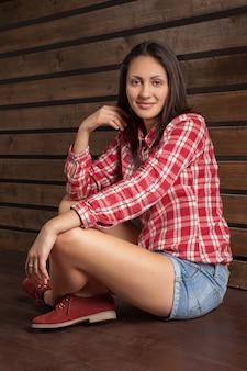 Jonge vrouw in cowboykleren over hout
