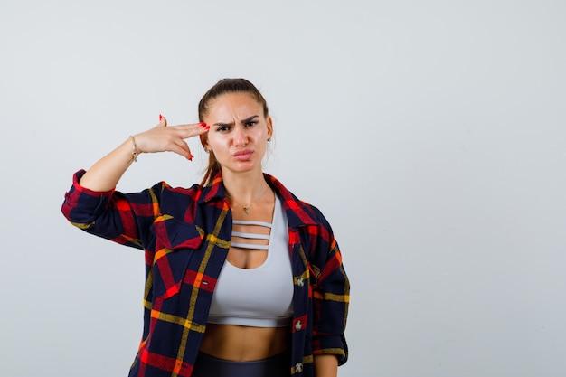 Jonge vrouw in crop top, geruit hemd, broek die zelfmoordgebaar maakt en er serieus uitziet, vooraanzicht.