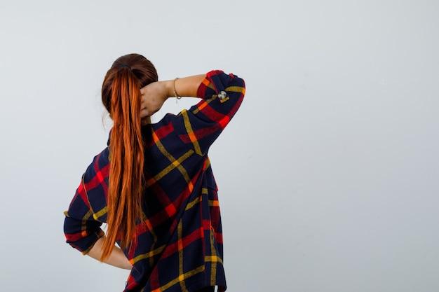Jonge vrouw in crop top, geruit hemd, broek met hand achter hoofd en peinzend, achteraanzicht.