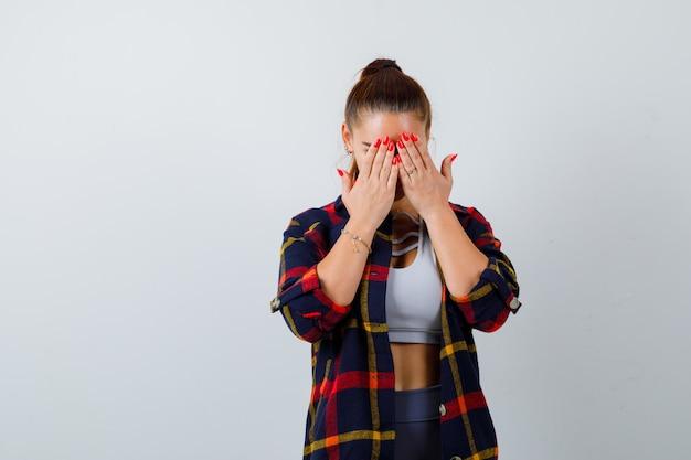Jonge vrouw in crop top, geruit hemd, broek met handen op het gezicht en weemoedig, vooraanzicht.