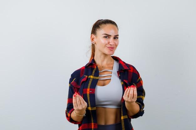 Jonge vrouw in crop top, geruit hemd, broek met italiaans gebaar en opgetogen, vooraanzicht.
