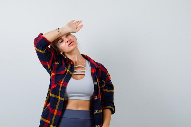 Jonge vrouw in crop top, geruit hemd, broek met pols op voorhoofd en uitgeput, vooraanzicht.