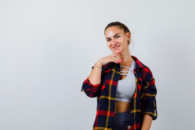 Jonge vrouw in crop top, geruit hemd, broek poseren terwijl ze staan en er vrolijk uitzien, vooraanzicht.