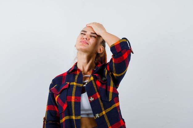 Jonge vrouw in crop top, geruit hemd met hand op voorhoofd en uitgeput, vooraanzicht.