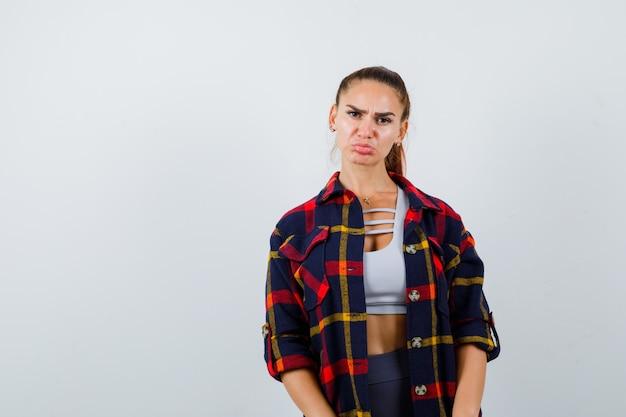 Jonge vrouw in crop top, geruit hemd pruilde lippen en keek beledigd, vooraanzicht.