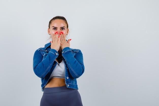 Jonge vrouw in crop top, jas, broek met handen op de mond en verbaasd, vooraanzicht.