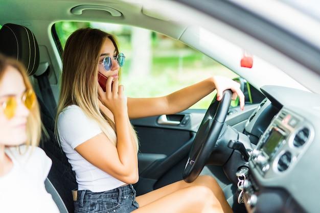 Jonge vrouw in de auto terwijl de bestuurder die mobiele telefoon met behulp van en concentratie verliest.
