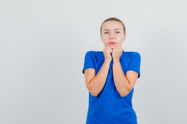 Jonge vrouw in de blauwe kraag van de t-shirtholding en het kijken