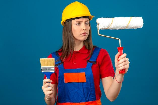 Jonge vrouw in de bouw eenvormige en gele de holdingsborstel van de veiligheidshelm en verfrol en het bekijken het met ernstig gezicht die zich op blauwe achtergrond bevinden