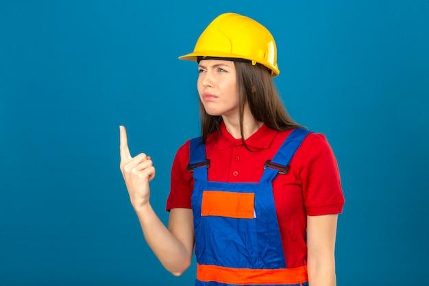 Jonge vrouw in de bouw eenvormige en gele veiligheidshelm die teleurstelling tonen die vinger op het ongelukkige kijken richten die zich op blauwe achtergrond bevinden
