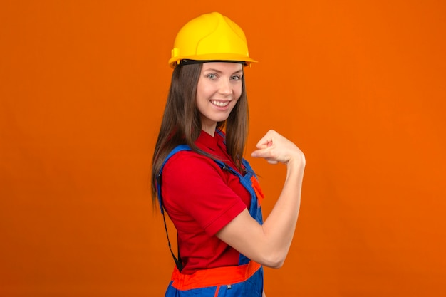 Jonge vrouw in de bouw uniforme en gele veiligheidshelm met haar biceps kunnen we het doen gebaar glimlachend staande op oranje achtergrond