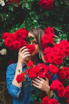 Jonge vrouw in de buurt van de struik van rode rozen in een tuin