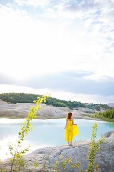 Jonge vrouw in de buurt van een meer met azuurblauw water en steenachtige bergen met groene bomen. prachtig uitzicht op het meer in het bos