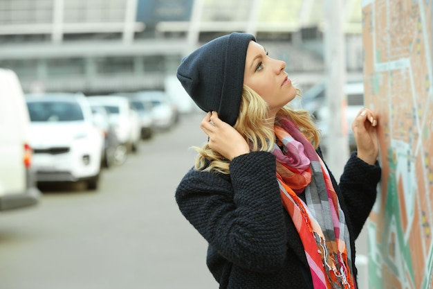 Jonge vrouw in de buurt van openbaar bord met stadsplattegrond, routes en locaties