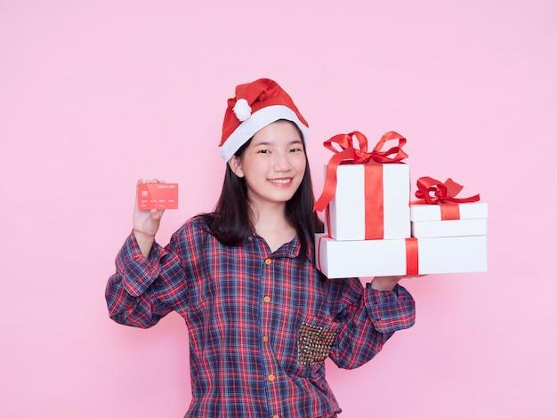 Jonge vrouw in de creditcard van de kerstmanhoed en giftdozen op roze muur.