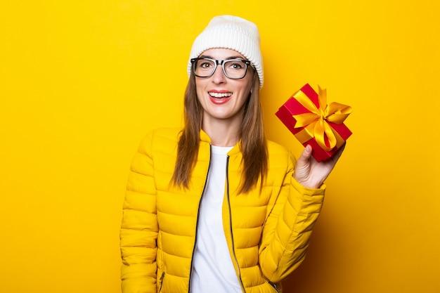 Jonge vrouw in de gele gift van de jasjeholding