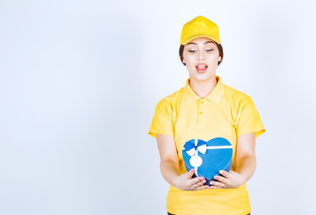 Jonge vrouw in de gele unishape die een doos in de vorm van een hart houdt en ernaar kijkt