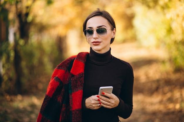 Jonge vrouw in de herfstpark die telefoon met behulp van