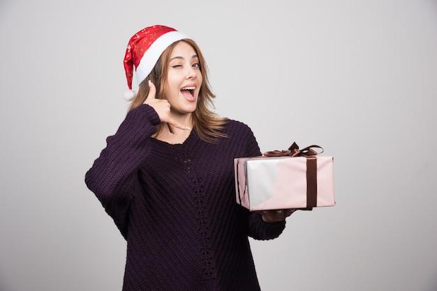 Jonge vrouw in de hoed van de kerstman met een cadeautje doet telefoongebaar met hand en vingers.