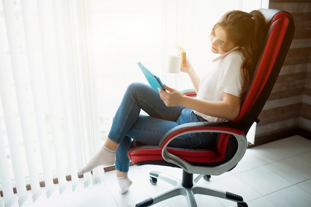 Jonge vrouw in de kamer. ga op de stoel bij het raam zitten en werk. zakenvrouw praten over de telefoon en tablet kijken. houd een kopje thee en een sandwich in de andere hand.