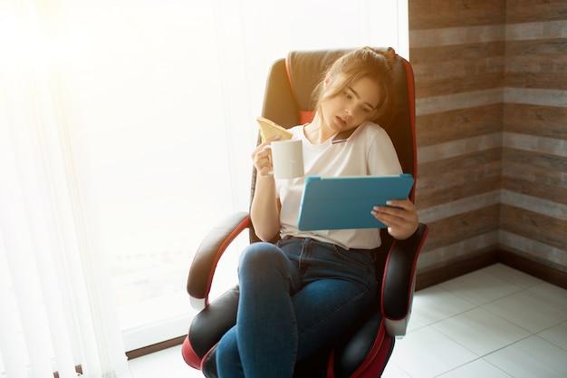Jonge vrouw in de kamer. ga op een stoel zitten en werk op afstand. praten over de telefoon en tegelijkertijd naar de tablet in handen kijken. zakenvrouw out-of-office in huis.