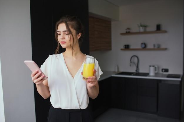 Jonge vrouw in de keuken tijdens de quarantaine. de onderneemster bekijkt ter beschikking smartphone en houdt glas jus d'orange. alleen thuis.
