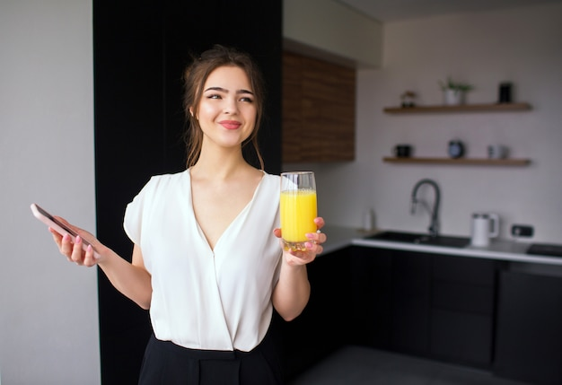 Jonge vrouw in de keuken tijdens de quarantaine. de telefoon en het glas van de meisjesgreep met jus d'orange in handen. positieve vrolijke zakenvrouw glimlach. werken op afstand in het thuiskantoor.